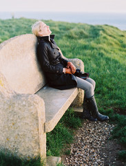 A woman seated on a stone bench on a coastal path.