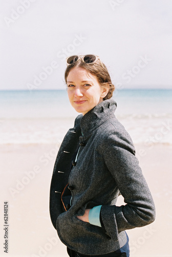 A woman in a grey coat on the beach.