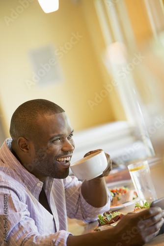 A man in a cafe holding a cup of coffee.