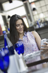 A cafe interior. A woman using a smart phone.