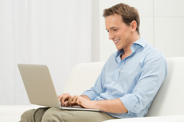 Man On Sofa With A Laptop