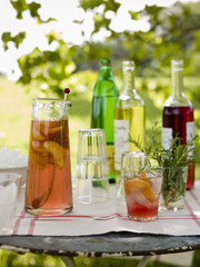 A buffet table set up in a garden for al  fresco meal. Drinks, bottles, a jug of punch and glasses.