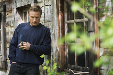 A  man with a blue jumper at home on his property.