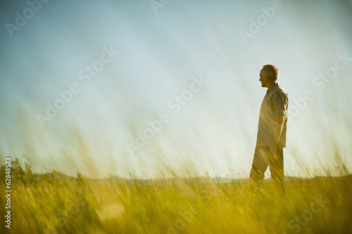 A man standing in grassland, looking into the distance.