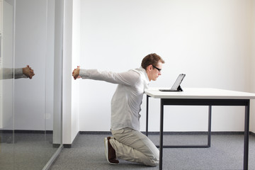 exercise during office work - man with tablet in his office