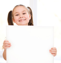 Cute girl is holding blank banner