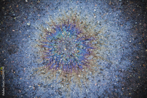Spilled oil on a road, creating a radiating pattern of multicoloured effect.