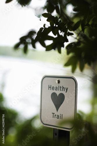 A health trail information sign, a metal marker path sigh with an image of a green heart.