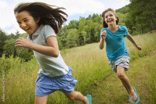 Two children, girls running and playing chase, laughing in the fresh air.