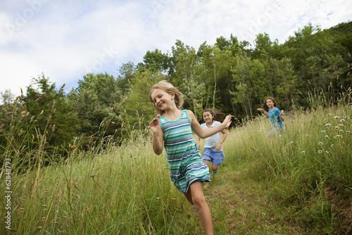 Three children, girls playing and laughing in the fresh air, chasing and racing through long grass.
