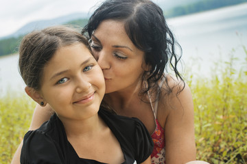 A mother and daughter in long grass by a lake shore.