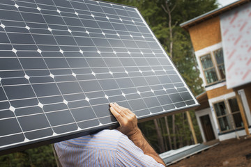 A workman carrying a large solar panel at a green house construction site.