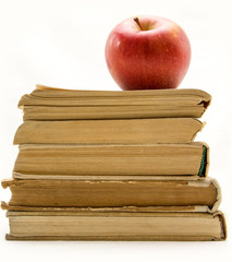 Stack of old books with red apple isolated