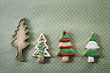Organic homemade Christmas cookies shaped like Christmas trees, iced with green, red and white icing.