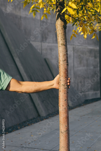 Man holding small tree, city sidewalk in background