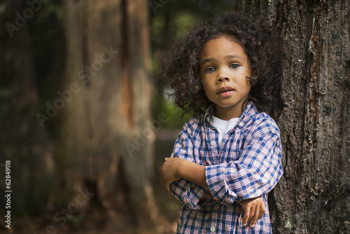 A young boy with arms folded leaning against a tree.