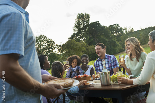 A family and friends sitting at a table outdoors having a meal.