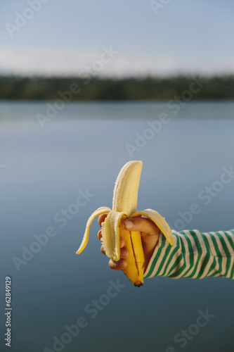 Nine year old girl holding organic, peeled banana