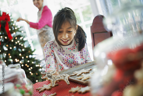 A young girl decorating Christmas cookies with icing.