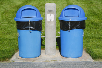 Blue trash cans on a grass sports field.