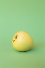 A single Golden Delicious apple on a green background.