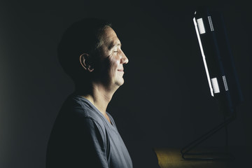 Smiling middle aged man sitting in front of a light therapy box, a full spectrum light box which mimics the sun, and treats people suffering from seasonal affective disorder.