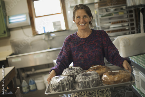 A woman in a kitchen carrying a tray of iced fresh baked cakes.