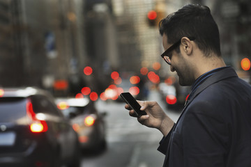 A man in a dark jacket checking his cell phone, standing on a busy street at dusk.