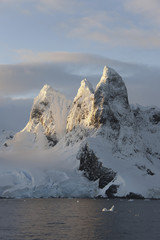 Sunrise on the mountain tops at the north entrance to the Lemaire Channel along the Antarctic Peninsula.