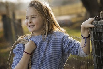 A young girl by a paddock fence.