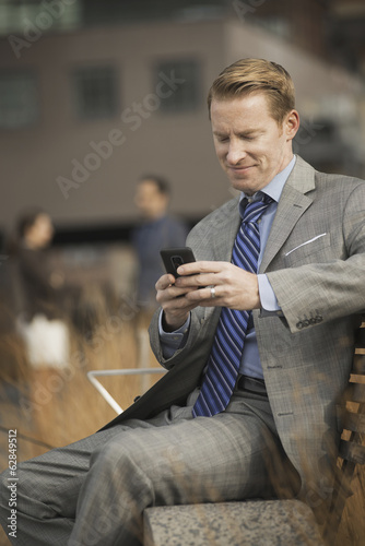 A man sitting on a bench outside a large building,  looking at a cell phone screen or mobile phone.