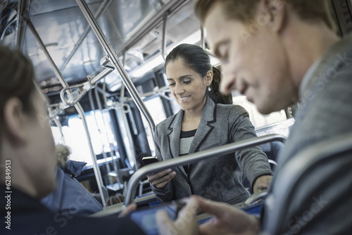 Business people in the city. Three people on the move, two men and a woman, on the bus.