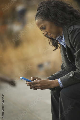 City life. A woman in a coat, checking and texting, keeping in contact, using a mobile phone.