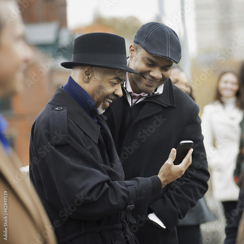 City life. Two men standing side by side, keeping in contact, using mobile phones, and checking the screen, laughing..