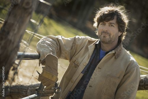 A man in a brown jacket, wearing work gloves leaning on a fence.  Working on an organic farm.