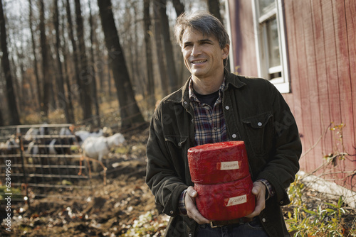 A man standing in a farm courtyard, holding two blocks of goat's cheese.