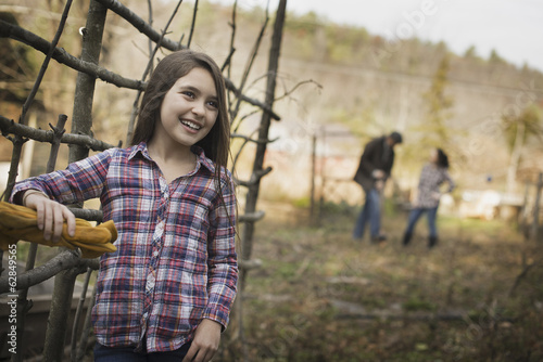 A young girl leaning on a fence, and two people in the background. An organic farm.