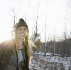 A young woman with blonde hair and a knitted woollen hat and coat. Outdoors on a winter's day. Snow on the ground.
