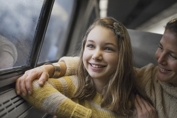 A man and a young girl sitting beside the window in a train carriage looking out at the countryside. Smiling in excitement.