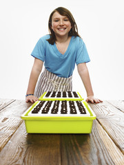 A young girl leaning on a table with two tray of freshly planted seeds resting on dark organic soil.