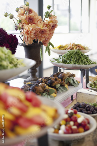 Organic prepared salads, vegetables and fruit on dishes, laid out for a party. A laden table. Flowers in a vase.  A farmstand food stall.