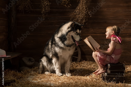Girl with a big dog in the barn