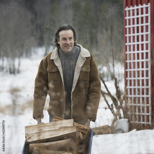 An organic farm in winter in New York State, USA. A man wheeling a barrow of firewood.