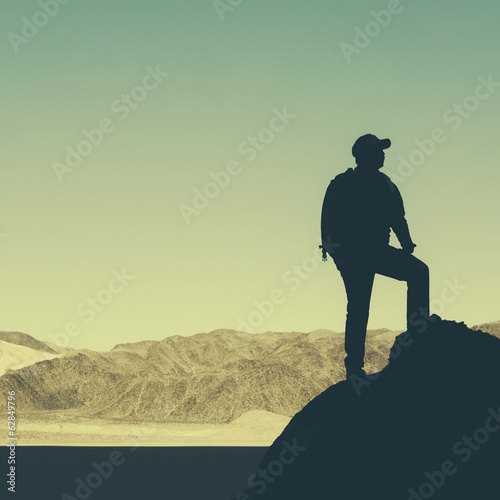Silhouette of a hiker wearing a backpack, pausing to take in view of mountains and desert in Death Valley National Park.