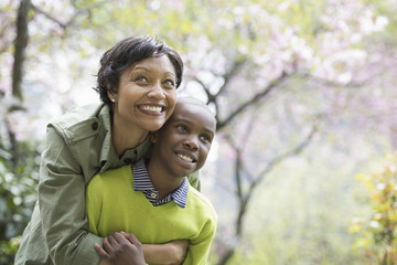 A New York city park in the spring. Sunshine and cherry blossom. A mother and son hugging and laughing.