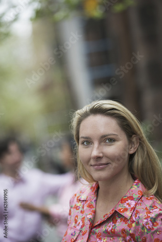City life in spring. A woman with long blonde hair looking at the camera.