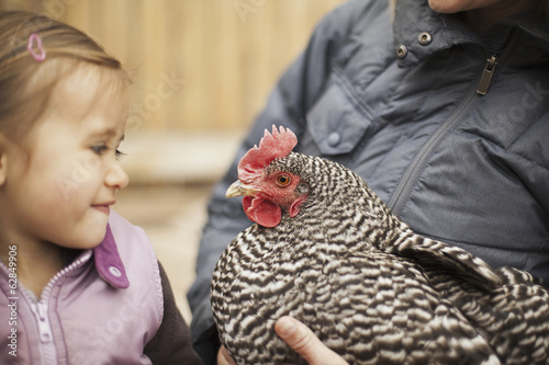 A woman in a grey coat holding a black and white chicken with a red coxcomb under one arm. A young girl beside her holding closely at the chicken.