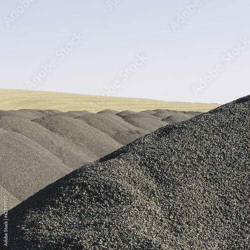 Gravel piles used for road maintenance and construction, a row of heaps near Pullman, Washington, USA.