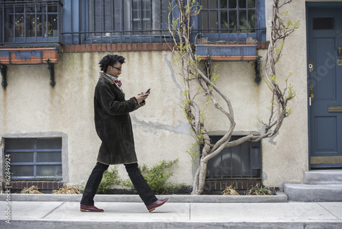 A woman in a warm coat walking along the street, checking her phone.