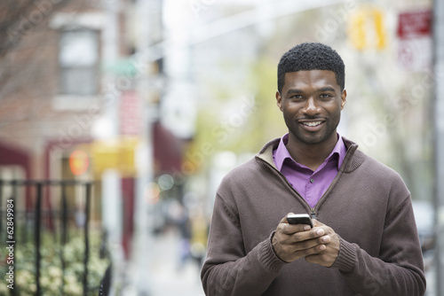 Outdoors in the city in spring. An urban lifestyle. A young man holding his phone, and smiling at the camera.